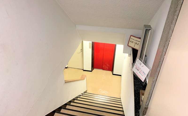 1F階段となります。赤いエレベーターの隣が当スペースのドアとなります。