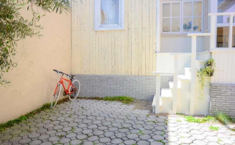 【ガーデン】石のタイルとベージュの壁面のスペースは赤い自転車もお使いいただけます
