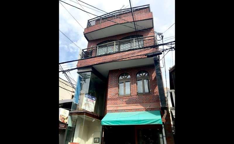 茶色のレンガの建物の2階にございます。
