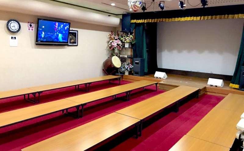 座卓12台まで使用可能。1テーブル4〜6人。(舞台カーテンは現在えんじ色です)